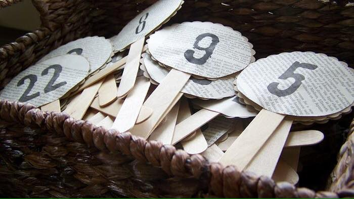 Numbered paddles in a brown basket.